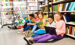 Children sitting on the floor in library and studying holding books